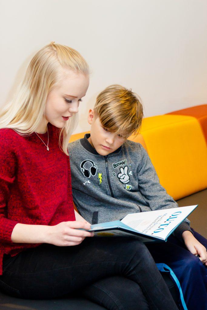 Nuori lukee lapselle kirjaa.