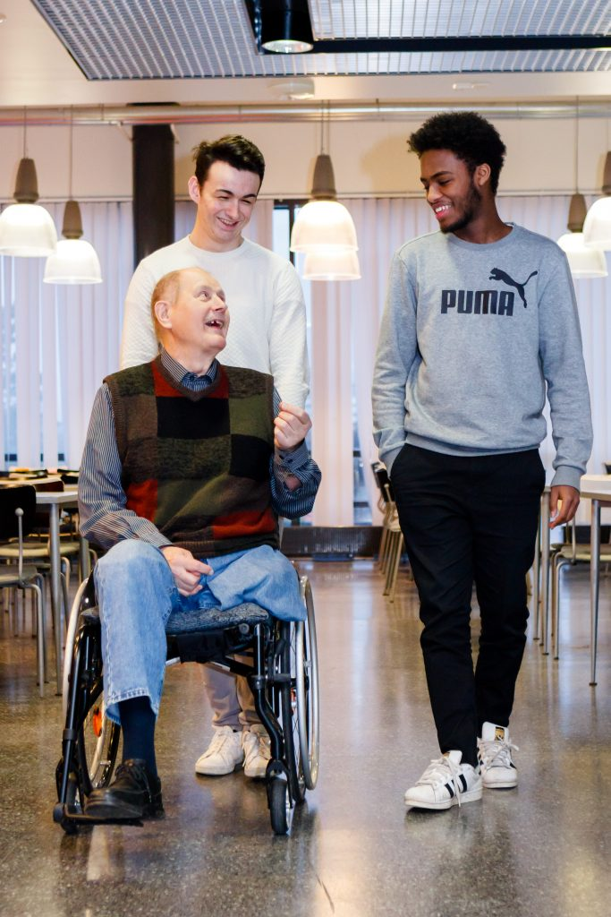 Kaksi nuorta kuljettaa pyörätuolissa olevaa senioria.