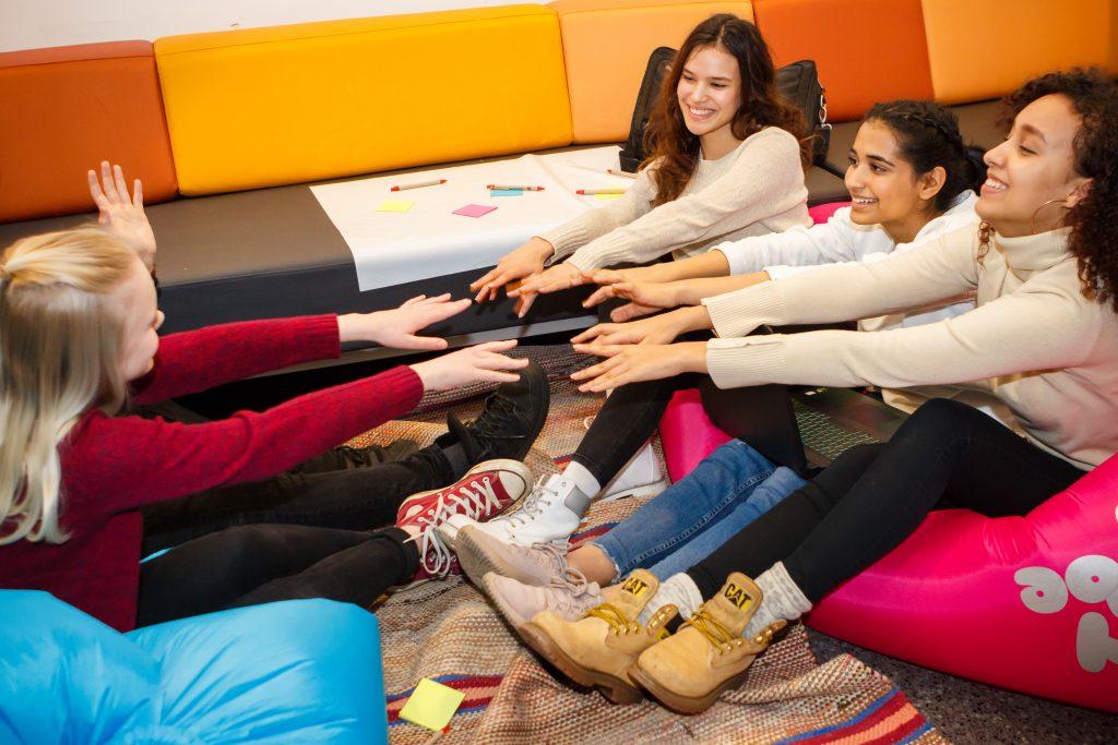 Ryhmä nuoria istuu lattialla ja kurottaa käsiään tosiaan kohti.