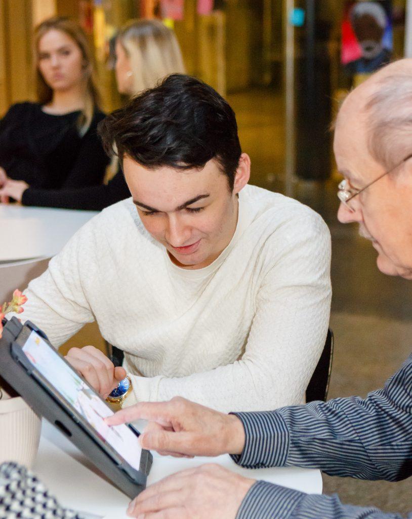 Nuori auttaa vanhempaa henkilöä tabletin kanssa.