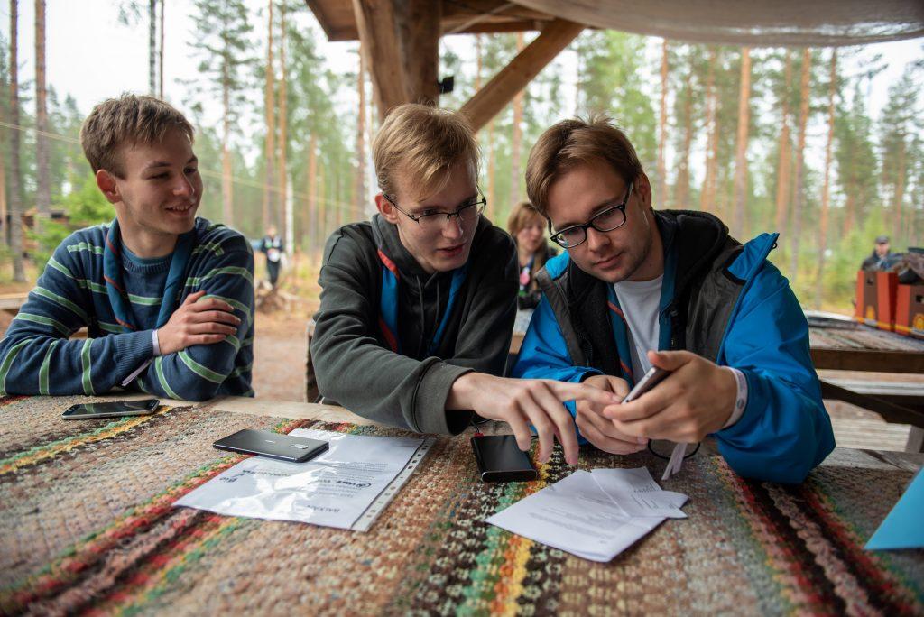 Kolme nuorta partiolaista kumartuneina kännykän ääreen