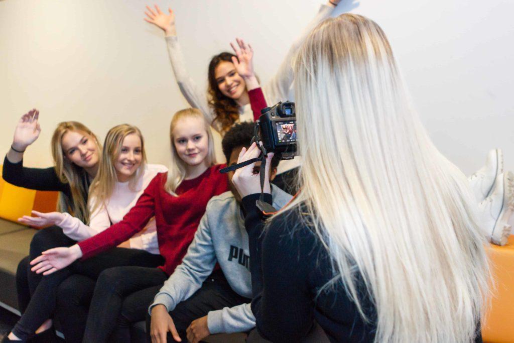 Nuori ottaa kuvaa ryhmästä hymyileviä nuoria.