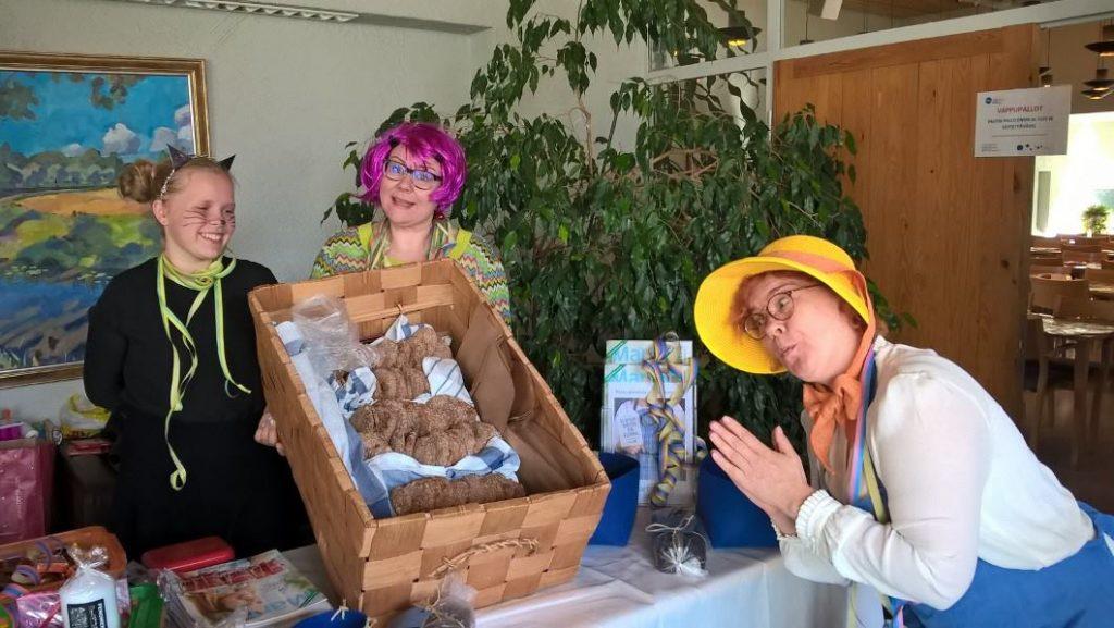 Maija-Lotta Vauramo Mynämäeltä kahden muun naisen kanssa myymässä leipää ja muita tuotteita. Naiset ovat pukeutuneet hauskasti vapun kunniaksi.