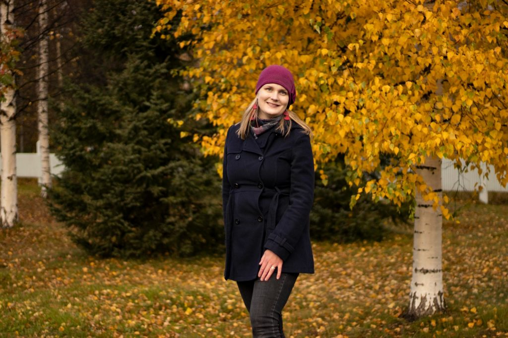 Tiia Brockman Oulusta seisoo syksyisessä maisemassa keltalehtisen koivun edessä.
